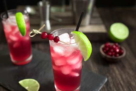 Cranberry Vodka Cocktail with lime and ice on black table. Cape Codder Cocktail with cranberry juice and vodka, alcohol drink. 스톡 콘텐츠