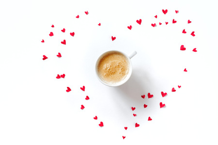 Cup of coffee and red hearts isolated on white background, copy space. Minimal flat lay with capuccino coffee for Valentine day, love and romance concept, top view.