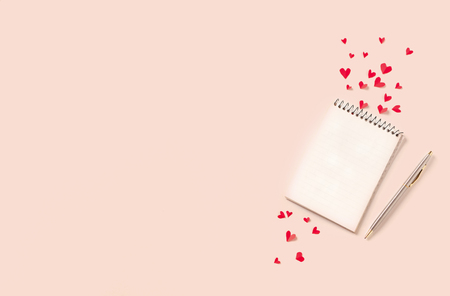 Notebook and red hearts isolated on beige background, copy space. Minimal flat lay with planning for Valentine day, love and romance concept, top view.