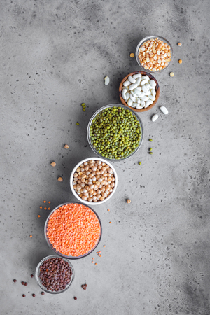 Assortment of colorful legumes in bowls, lentils,  kidney beans, chickpeas, mung, peas on concrete background, top view, copy space. Healthy food, dieting, nutrition concept, vegan protein source. Stok Fotoğraf