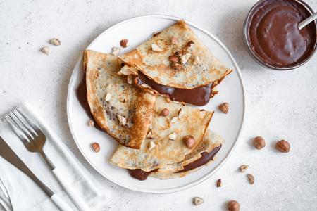 Crpes mit Schokoladenaufstrich und Haselnüssen. Hausgemachte dünne Crpes zum Frühstück oder Dessert auf weißem Hintergrund, Kopienraum.