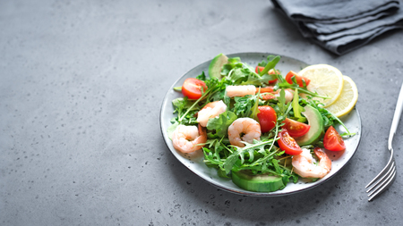 Avocado Shrimp Salad with Arugula and Tomatoes on grey stone background, copy space. Healthy diet green salad with Shrimps (prawns), avocado, cherry tomato and arugula. Banque d'images