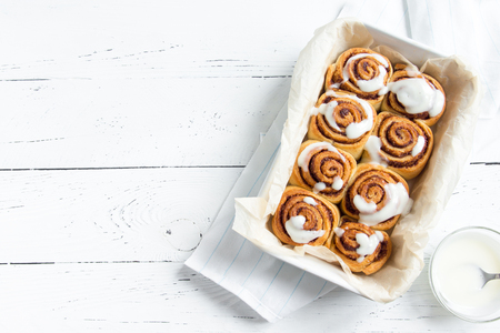 Cinnamon rolls or cinnabon, homemade sweet traditional dessert buns with white cream sauce on white wooden background, copy space.