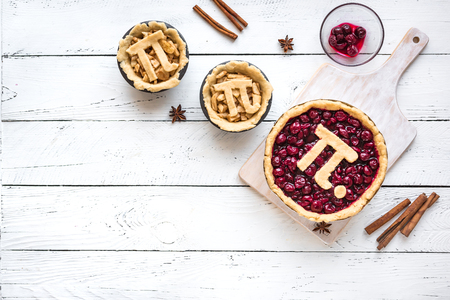 Pi Day Cherry and Apple Pies - making homemade traditional various Pies with Pi sign for March 14th holiday, on white wooden background, top view, copy space. Stock Photo