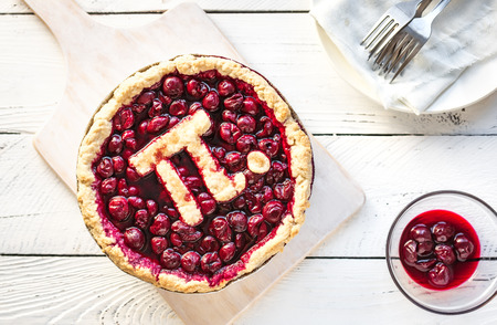 Pi Day Cherry Pie - Homemade Traditional Cherry Pie with Pi sign for March 14th holiday, on white wooden background, top view, copy space. Stock Photo