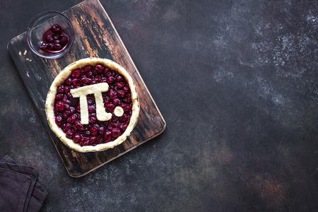 Pi Day Cherry Pie: elaboración de tarta de cereza tradicional casera con signo Pi para la fiesta del 14 de marzo, sobre fondo rústico, vista superior, espacio de copia. Foto de archivo