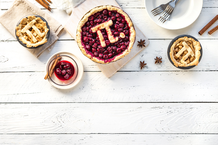 Pi Day Cherry and Apple Pies - homemade traditional various Pies with Pi sign for March 14th holiday, on white wooden background, top view, copy space. Reklamní fotografie