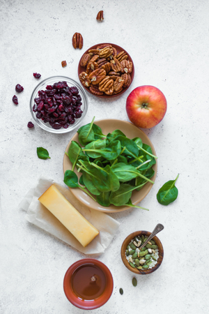 Healthy Salad Ingredients for cooking healthy vegan salad - baby spinach leaves, apple, pecan nuts, dry cranberries. Clean eating or diet food ingredients on white background, copy space. Stock Photo