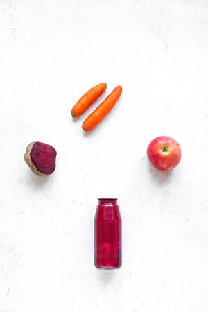 Purple smoothie bottle and ingredients (beet, carrot, apple) on white background, copy space, top view. Making detox diet vegan healthy smoothie or juice.
