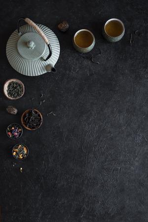 Various Tea Selection, Teapot and Teacups on black background, copy space. Traditional asian tea arrangement  -  iron teapot and ceramic teacups with tea.