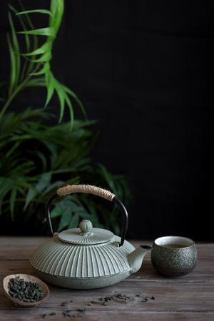 Teekanne und Teetassen auf schwarzem Hintergrund, Kopienraum. Traditionelles asiatisches Arrangement für Teezeremonie - Eisenteekanne und Keramikteetassen mit Tee. Standard-Bild