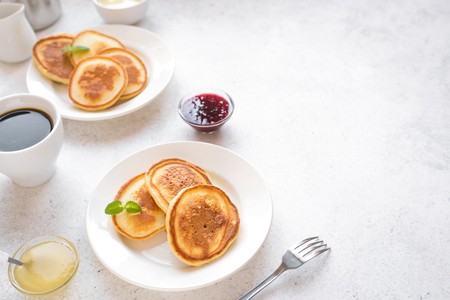 Pancakes for breakfast. Homemade pancakes with various toppings, jam, honey and coffee - breakfast for two, weekend family breakfast, top view, copy space. Foto de archivo
