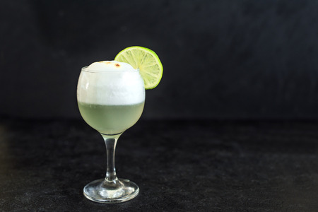 Pisco Sour Cocktail. Peruvian, Mexican, Chilean traditional drink pisco sour liqueur with  lime and egg on black background.