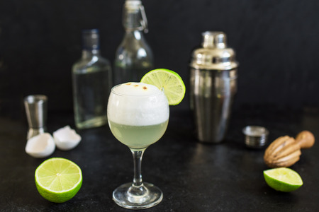 Pisco Sour Cocktail. Peruvian, Mexican, Chilean traditional drink pisco sour liqueur with  lime and egg and bar equipment for making.
