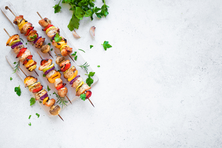 Grilled Chicken and Vegetable Skewers with  bell peppers, zucchini, onion and mushrooms on white background, top view, copy space. Meat and vegetables kebabs on skewers.