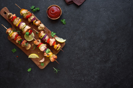 Grilled Chicken and Vegetable Skewers with bell peppers, zucchini, onion and mushrooms on black background, top view, copy space. Meat and vegetables kebabs on skewers. Stock Photo