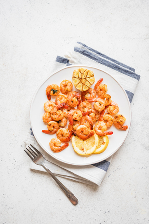 Roasted shrimps with lemon, garlic and herbs. Seafood, shelfish. Shrimps Prawns sauteed with spices, garlic and lemon on white background, copy space. Shrimps prawns on plate.