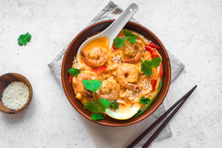 Laksa Shrimp Soup. Prawn noodle laksa soup on white background, top view, copy space. Asian Malaysian food.