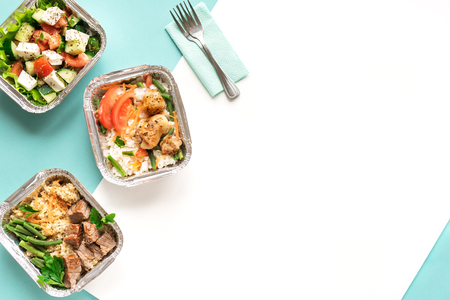 Healthy food delivery. Take away of organic daily meal on blue, copy space. Clean eating concept, healthy food, fitness nutrition take away in boxes, top view. Stock Photo
