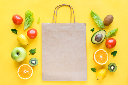 Healthy food background. Healthy food and paper bag vegetables and fruits on yellow, copy space. Shopping food supermarket concept.