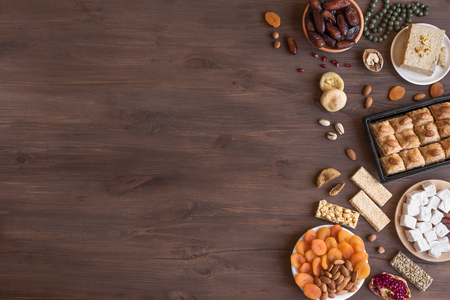 Assortment, set of Eastern, Arabic, Turkish sweets, nuts and dried fruits on wooden table, top view, copy space. Holiday Middle Eastern traditional sweet food. Stock fotó