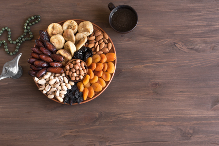 Dried Fruits and Nuts on platter, top view. Vegetarian healthy sweets on wooden, copy space. Traditional Muslim Iftar food for Ramadan. Banque d'images