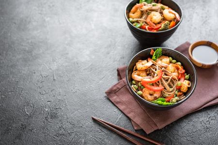 Stir fry with soba noodles, shrimps (prawns) and vegetables. Asian healthy food, stir fried meal in bowl on black background, copy space.
