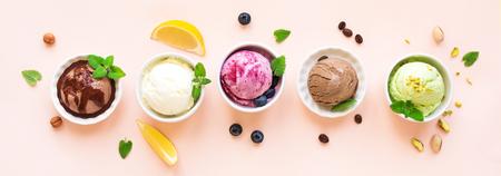 Asortyment lodów. Różne lody owocowe i jagodowe na różowym tle, baner. Mrożony jogurt lub lody ekologiczne - zdrowy letni deser. Zdjęcie Seryjne