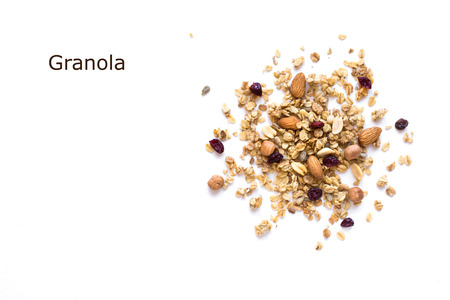 Granola creative layout isolated on white background, copy space. Healthy snack or breakfast concept - homemade granola with grains, dry cranberries and nuts.