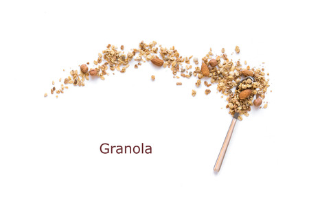 Nut Granola on spoon isolated on white background, copy space. Healthy snack or breakfast concept - homemade granola with grains and nuts.