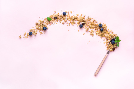 Homemade Granola on spoon with bluberries on pink background, copy space. Healthy snack or breakfast concept - granola with grains, nuts, dry fruits, berries.
