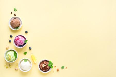 Ice Cream Assortment. Various fruit and berries ice creams on yellow background, copy space. Frozen yogurt or ice cream - healthy summer dessert. Stock Photo