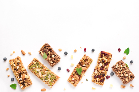 Various granola bars isolated on white background, copy space. Homemade healthy snack - granola superfood bars.