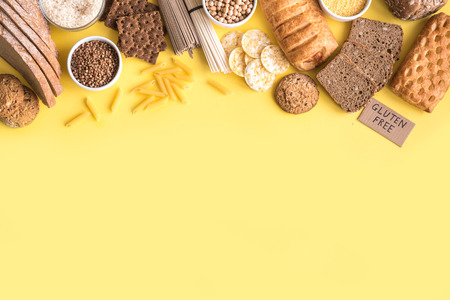 Gluten free food. Various gluten free pasta, bread, snacks and flour on yellow background, top view, copy space.