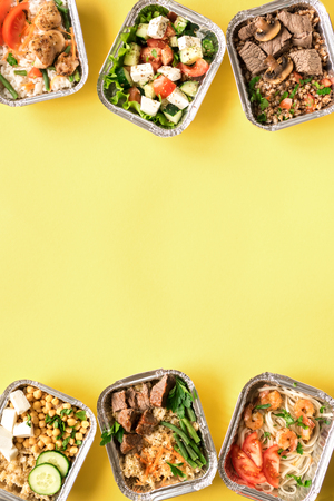 Healthy food delivery. Take away of organic daily meal on yellow, flat lay. Clean eating concept, healthy food, fitness nutrition take away in foil boxes, top view.