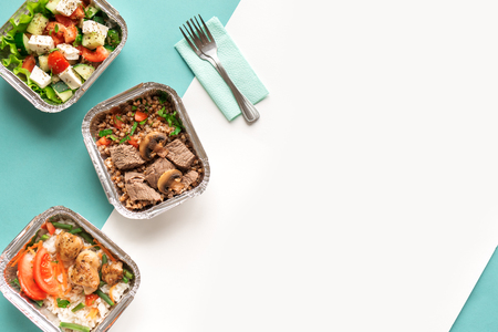 Healthy food delivery. Take away of organic daily meal on white and blue, flat lay. Clean eating concept, healthy food, fitness nutrition take away in foil boxes, top view.