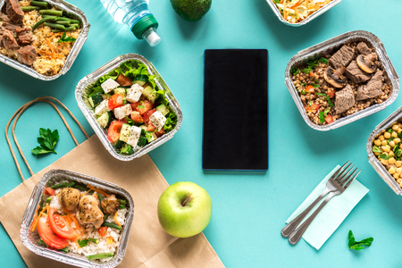 Healthy food delivery. Take away of organic daily mealon blue, flat lay. Clean eating concept, healthy food, fitness nutrition take away in foil boxes, top view. Imagens