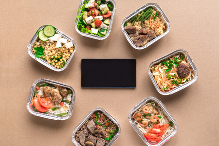Healthy food delivery. Take away of organic daily meal, copy space. Clean eating concept, healthy food, fitness nutrition take away in foil boxes, top view, flat lay.
