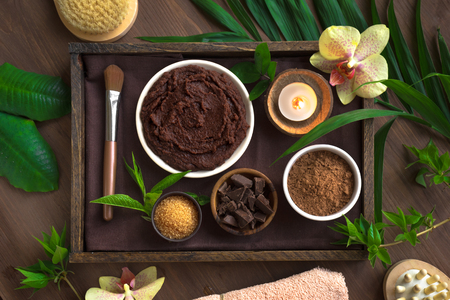 Chocolate Spa composition with plants and flowers, flat lay, copy space. Natural spa chocolate products and organic treatment concept on dark wooden background.