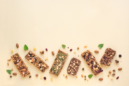 Granola bars assortment on yellow background, copy space. Homemade healthy snack - granola superfood bars.