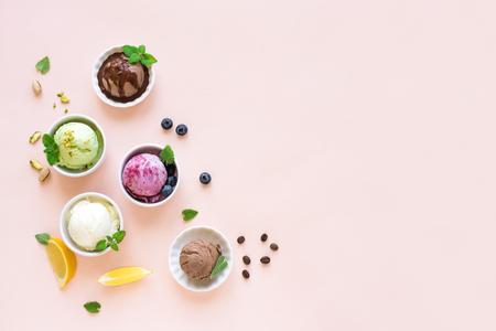 Asortyment lodów. Różne lody owocowe i jagody na różowym tle, miejsce. Mrożony jogurt lub lody ekologiczne - zdrowy letni deser. Zdjęcie Seryjne