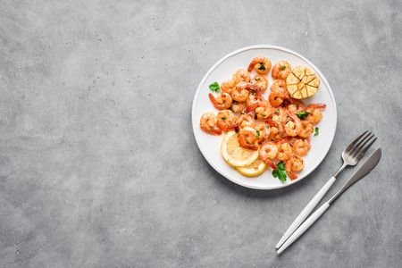 Roasted shrimps with lemon, garlic and herbs. Seafood, shelfish. Shrimps Prawns grilled with spices, garlic and lemon on grey stone background, copy space. Shrimps prawns on plate.