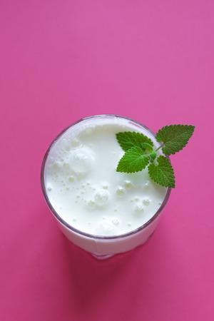 Yogurt drink (ayran, kefir, lassi) in glass - healthy summer refreshing cold drink on pink, copy space.