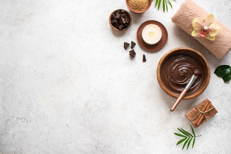 Chocolate Spa flat lay on white background, top view, copy space. Natural spa beauty products with chocolate and plants.