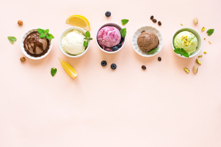 Ice Cream Assortment. Various ice creams in bowls on pink background, copy space. Frozen yogurt or organic ice cream - healthy summer dessert.