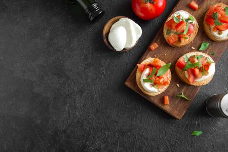 Italiaanse bruschetta met gehakte tomaten, basilicum, mozzarella kaas en balsamico azijn. Verse zelfgemaakte caprese bruschetta of crostini op zwarte stenen achtergrond, kopie ruimte. Stockfoto