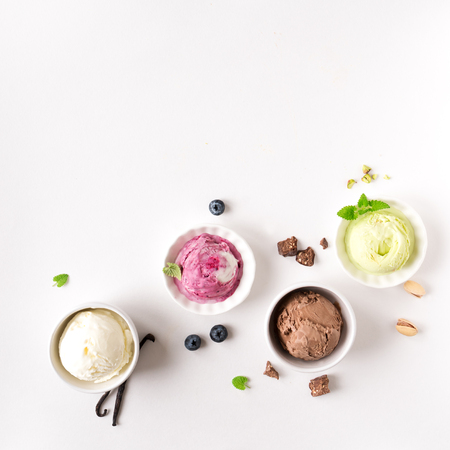 Ice Cream Assortment. Various ice creams and ingredients on white background, copy space. Frozen yogurt or ice cream in cups - healthy summer dessert. Banque d'images