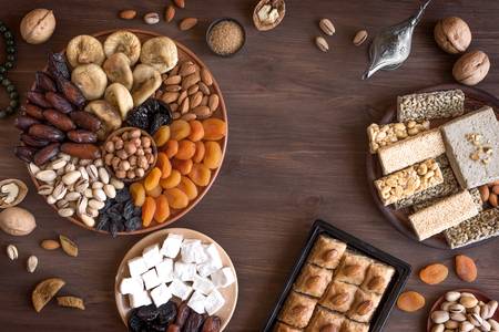 Assortment, set of Eastern, Arabic, Turkish sweets, nuts and dried fruits on wooden table, top view, flat lay. Holiday Middle Eastern traditional sweet food. Zdjęcie Seryjne