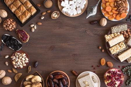 Sortiment, östliche, arabische, türkische Süßigkeiten, Nüsse und Trockenfrüchte auf Holztisch, Draufsicht, Kopierraum. Traditionelles süßes Essen im Nahen Osten. Standard-Bild