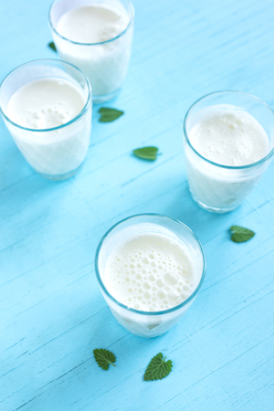 Ayran, homemade yogurt drink (kefir, lassi) with cucumbers - healthy summer refreshing cold drink on blue, copy space. Imagens - 123140520